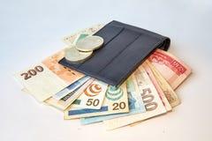 Achtergrond, zwarte mensen` s portefeuille met geïsoleerde rekeningen van diverse munten, stock foto