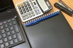 Achtergrondcalculator en notitieboekje op een bureau Stock Foto's