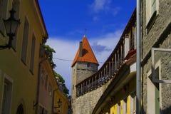 Achtergrondlandschapsmening van de bochtige straat van de oude stad in Tallinn, en de oude vestingsmuur met toren stock foto