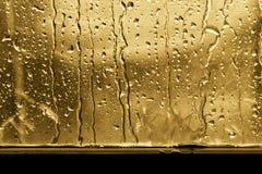 Achtergrondregendruppel op het goud van het vensterglas of geel stock foto