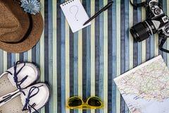 Achtergrondsamenstelling van hierboven voor de zomervakantie met uitstekende camera, zonnebril, witte schoenen, strohoed, kaart e stock foto
