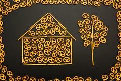 Achtergrondtextuur van gezouten pretzels en ministokken in de vorm van een huis en een boom op een zwarte achtergrond stock foto's