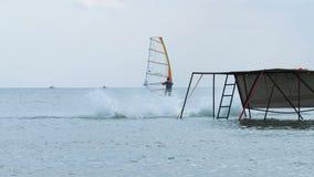 Achtergrondvideo van de tieners die van de de zomervakantie in het zeewater van de pijler dichtbij de raad met een zeil springen stock footage