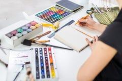 Achterhoekmening van een kunstenaar die nieuw beeld creëren die potloden, pastelkleur, verven en borstels in sketchbook gebruiken stock afbeelding