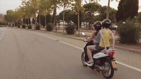 Achterkant twee jonge meisjesaandrijving op autoped in stad De avond van de zomer Groene Bomen Mensen Warme Schaduwen stock footage