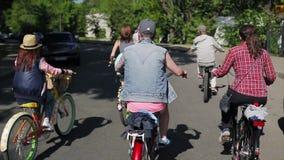 Achterkant van cirkelende groep mensen in de zomerdag Langzame Motie stock videobeelden