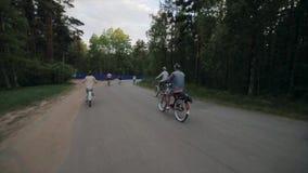 Achterkant van cirkelende groep mensen in een park in de zomeravond Langzame Motie stock footage