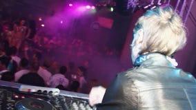 Achterkant van DJ in leer jaket bij draaischijf in overvolle nachtclub Ga gaan meisjes stock footage