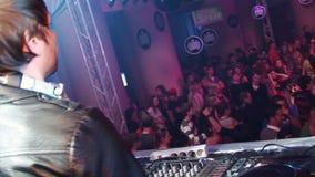 Achterkant van DJ in leer jaket bij draaischijf in overvolle nachtclub hoofdtelefoons stock footage