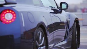 Achterkant van donkerblauwe coupé nieuwe auto op straat wielen presentatie Rood lichten auto Koude schaduwen stock footage