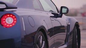 Achterkant van donkerblauwe nieuwe auto wielen presentatie Rood lichten bumper auto Koude schaduwen stock videobeelden