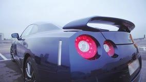 Achterkant van donkerblauwe nieuwe coupéauto presentatie Rood lichten bumper auto Koude schaduwen stock videobeelden