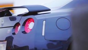 Achterkant van nieuwe auto van de bumper de donkerblauwe coupé presentatie Rood lichten auto Koude schaduwen stock video