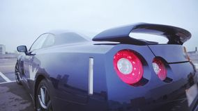 Achterkant van nieuwe donkerblauwe coupéauto op straat bumper presentatie Rood lichten auto Koude schaduwen stock videobeelden