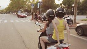 Achterkant van twee meisjes in helmenaandrijving op autoped in stad De avond van de zomer Groene Bomen Warme Schaduwen stock videobeelden