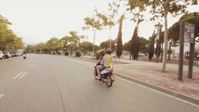 Achterkant van twee meisjesaandrijving op autoped in stad De avond van de zomer Park met groene bomen Warme Schaduwen stock video