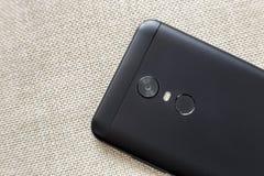 Achterkant van zwarte die cellphone met het apparaat van het de vingerafdrukaftasten van de veiligheidsduim, camera en flitsverli royalty-vrije stock fotografie