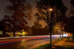 Achterlichten van auto op weg in donkere mistige de winteravond Stock Foto