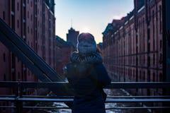Achtermeisjesmening Meisje die zich op de brug bevinden die op het moderne gebouw letten de zonsondergang en het zachte licht Ham royalty-vrije stock foto's