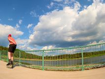 Achtermening aan gealigneerde schaatser die in rode t-shirt en zwarte broek op de brug schaatsen Het openlucht gealigneerde schaa royalty-vrije stock foto's