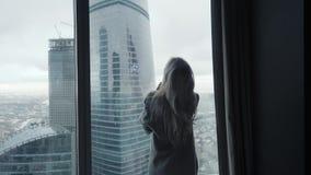 Achtermening bij Mooie blondevrouw status die uit het venster van gemiddelde lengte van luxe moderne flat of hotelruimte kijken stock video