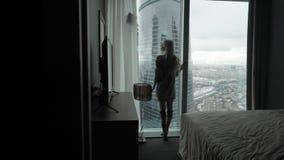 Achtermening bij Mooie blondevrouw status die uit het venster van gemiddelde lengte van luxe moderne flat of hotelruimte kijken stock videobeelden