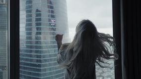 Achtermening bij Mooie blondevrouw status die uit het venster van gemiddelde lengte van luxe moderne flat of hotelruimte kijken stock footage