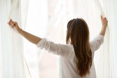 Achtermening bij vrouw het openen venstergordijnen die van goedemorgen genieten stock foto