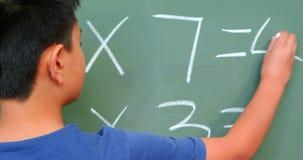 Achtermening die van Aziatische schooljongen wiskundeprobleem aangaande bord in klaslokaal oplossen op school 4k stock footage