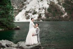 Achtermening die van bruid en bruidegom, zich op de meerkust bevinden met toneelbergmening in Polen Morskie Oko stock afbeelding