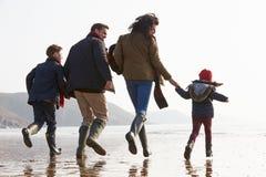 Achtermening die van Familie langs de Winterstrand lopen stock foto