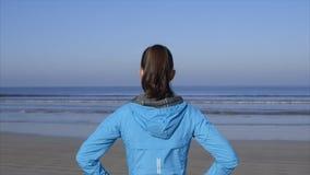 Achtermening die van geschikte vrouw zich op strand het letten op golven bevinden stock video