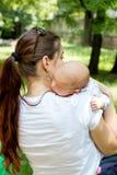 Achtermening die van het houden van van gelukkige moeder gevende leuke baby, de baby geven die aan oprisping na maaltijd, baby he royalty-vrije stock foto