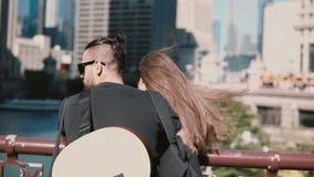 Achtermening die van jong mooi paar die zich op de brug bevinden, van de mening van Chicago, Amerika genieten Mens met gitaar stock footage