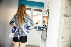 Achtermening die van jonge vrouw klaar voor keuken het schoonmaken worden stock foto's