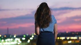 Achtermening die van jonge vrouw wapens in de lucht opheffen die en van mening van prachtige scharlaken hemel ontspannen genieten stock footage