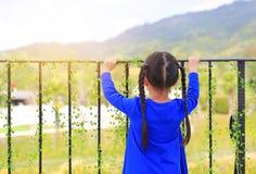Achtermening die van meisje zich bij balkonbars bevinden en uit aan aard de ochtend bekijken stock foto