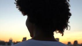 Achtermening die van mooie vrouw die van zonsondergang in stad genieten, zich op dak, rust bevinden stock videobeelden