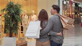 Achtermening die van paarholding het winkelen zakken wordt geschoten, zoekend een winkel bij de wandelgalerij stock videobeelden