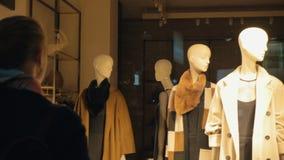 Achtermening die van vrouw naar het winkelvenster gaan met vrouwelijke ledenpoppen stock video