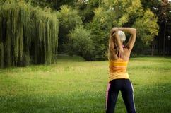 Achtermening, het jonge vrouw uitrekken zich vóór oefening in park stock afbeeldingen