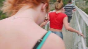 Achtermening over twee jonge vrouwen die op grote hangbrug over groene bergvallei en bergrivier lopen stock video