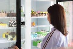 Achtermening van aantrekkelijke Aziatische vrouwelijke glimlach die cake kiezen bij bakkerijopslag stock fotografie