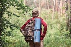 Achtermening van actieve backpacker die uitweg in bos zoeken, die slaapstootkussen en donkere rugzak met thermosflessen hebben bi royalty-vrije stock foto