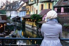 Achtermening van alleen Vrouw die bovenlaag aan een kant van kanaal dragen die aan Kleurrijke traditionele oude Franse huizen op  stock foto's