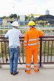 Achtermening van architecten die zich tegen traliewerk bij bouwwerf bevinden Stock Foto's