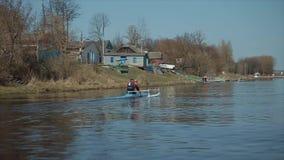 Achtermening van Atleet het roeien op de rivier in een kano Het roeien, canoeing, het paddelen Opleiding kayaking Volgend schot stock video