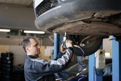 Achtermening van automobiele mechanische het onderzoeken auto in workshop stock foto's