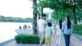 Achtermening van Aziatische familie van 4 die op de promenade van de waterkant bij schemer lopen stock footage
