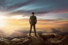 Achtermening van Aziatische zakenman op de bovenkant van de heuvel die wo eruit zien royalty-vrije stock foto